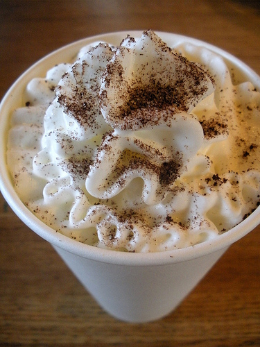 кофе мокко со взбитыми сливками и пудрой какао в бумажном стаканчике