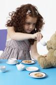 Девочка угощает кофе плюшевого медведя